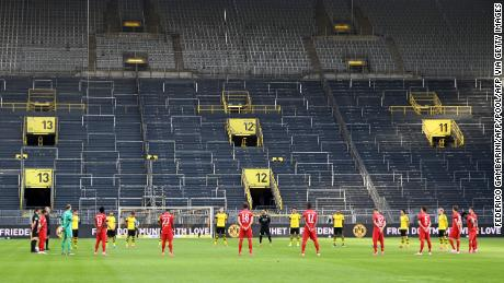 The players observe a minute of silence for the victims of the coronavirus before the football game of the German Bundesliga First Division, Borussia Dortmund and FC Bayern Munich.