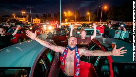 Fans cheer as they watch the Czech First Division soccer match between FC Viktoria Plzen and AC Sparta Praha at a drive-in cinema in Plzen, Czech Republic.