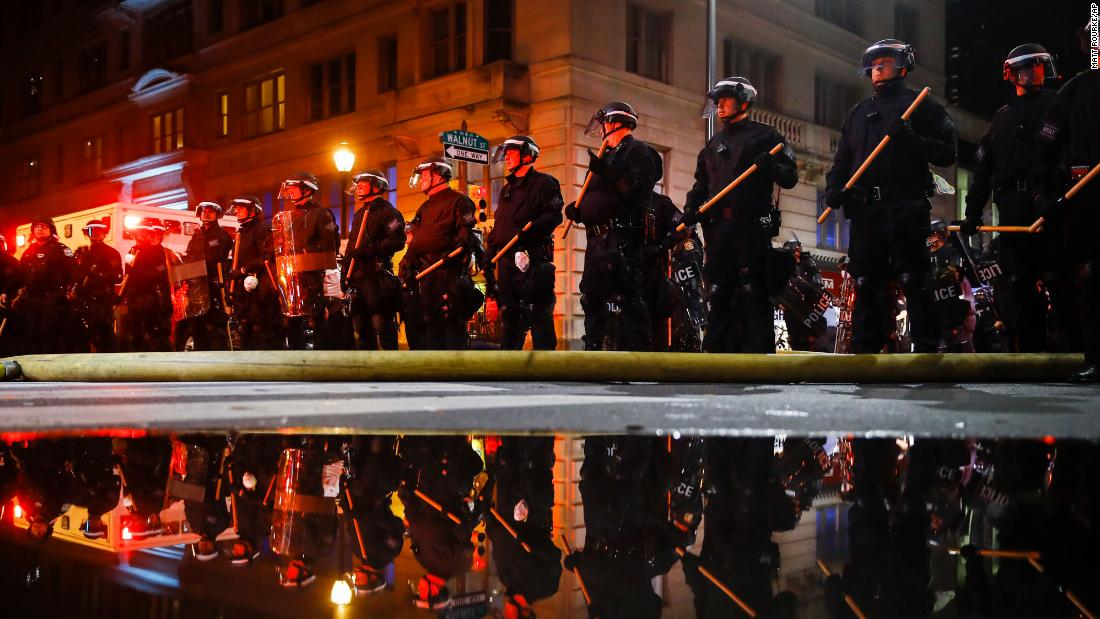 Philadelphia police are reflected as they stand guard during a protest over the death of George Floyd on Saturday, May 30, 2020.