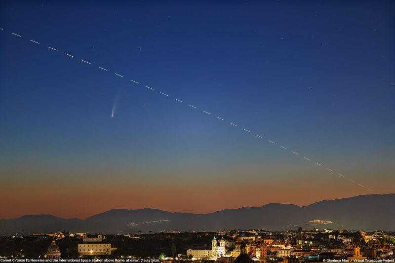 Twilight horizon over city with small streak and white dashed line against deep blue sky.