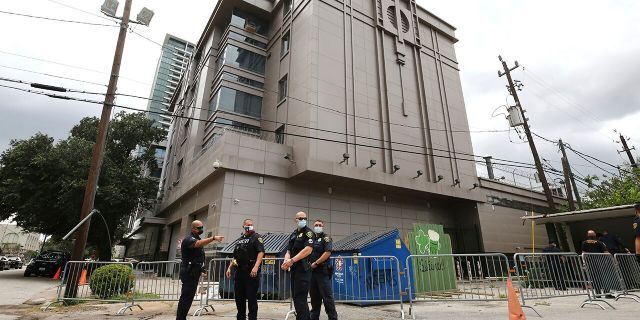 Police officers install barricades outside the Consulate General of China Friday, July 24, 2020, in Houston. Workers at China's consulate loaded up moving trucks Friday ahead of an afternoon deadline to shut down the facility, as ordered by the Trump administration. (Godofredo Vasquez/Houston Chronicle via AP)