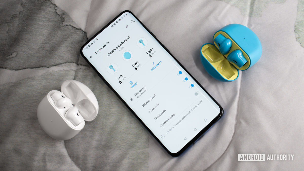 A picture of the OnePlus Buds true wireless earbuds in white and Nord Blue next to a OnePlus 7 Pro smartphone with the earbuds menu pulled up on the screen.