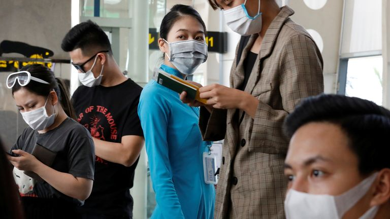 A Vietnam Airlines worker and passengers are seen wearing protective masks at Danang airport