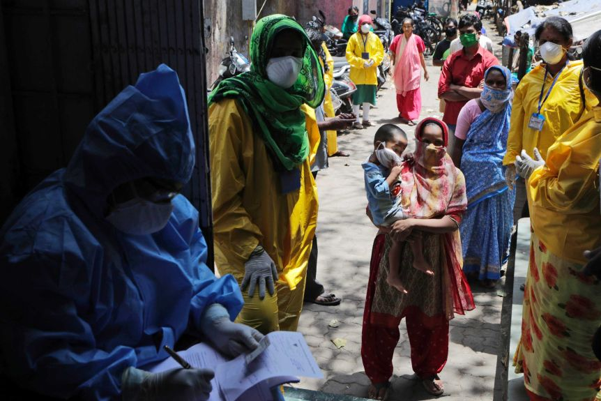 People wait to give their samples to medical staff at a slum area during India's lockdown.