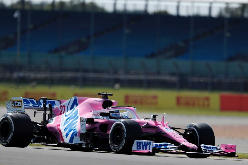A pink F1 racing car is seen on a race track
