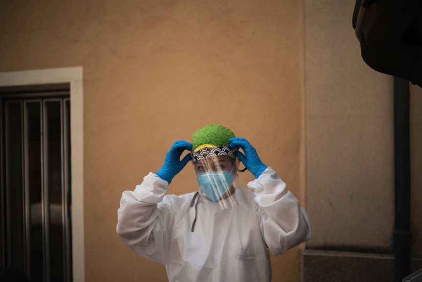 A doctor fixes a protective mask to her face with gloved hands