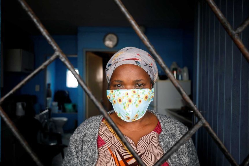 A woman in a face mask looks through a barred window