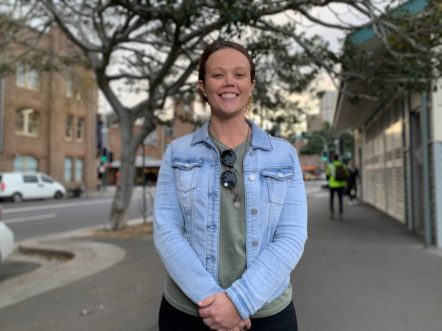 A woman in a denim jacket stands on a footpath.