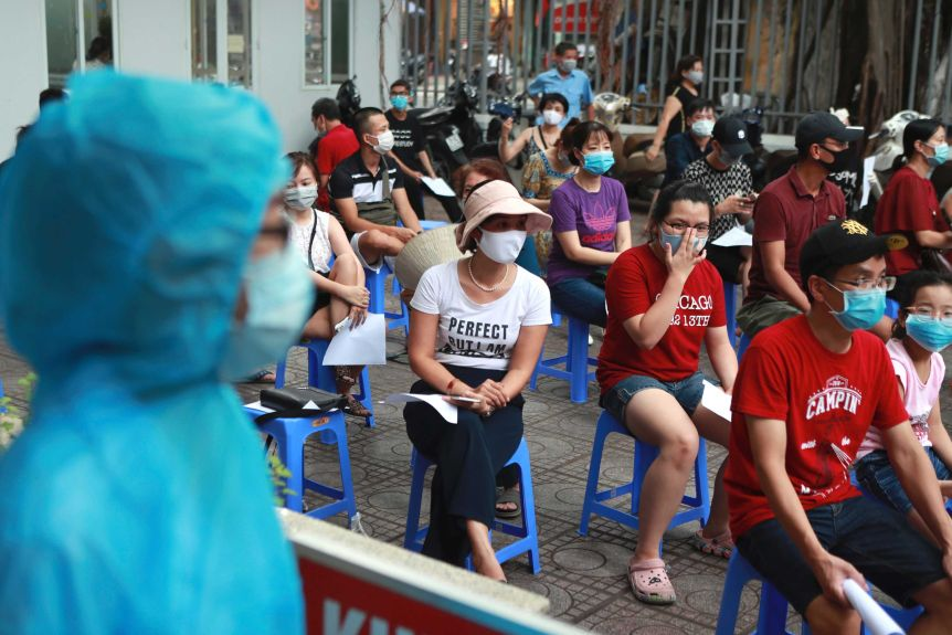 People in face masks sit waiting on plastic stools outdoors.