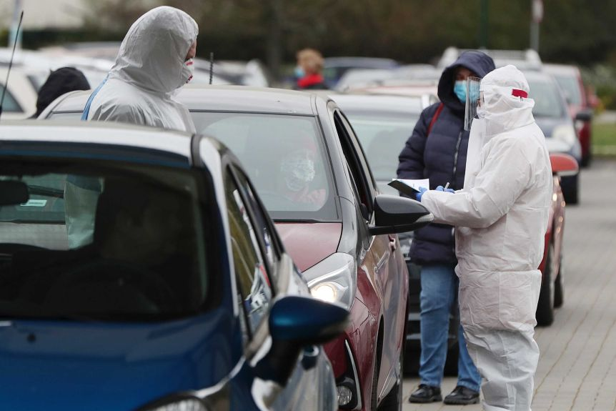 Two people in PPE stand around a car as one of them examines some paperwork
