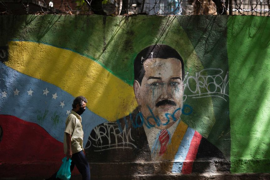A man wearing a face mask walks past a mural of Venezuelan President Nicolas Maduro