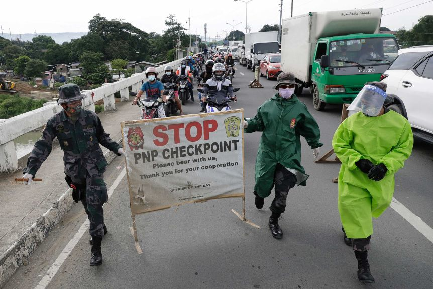 Two men in fatigues carry a sign saying 'Stop: PNP checkpoint' ahead of a long line of traffic.