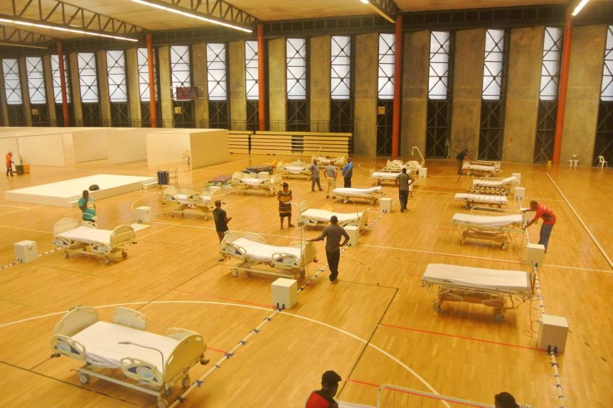 People stand in a large room setting up hospital beds.