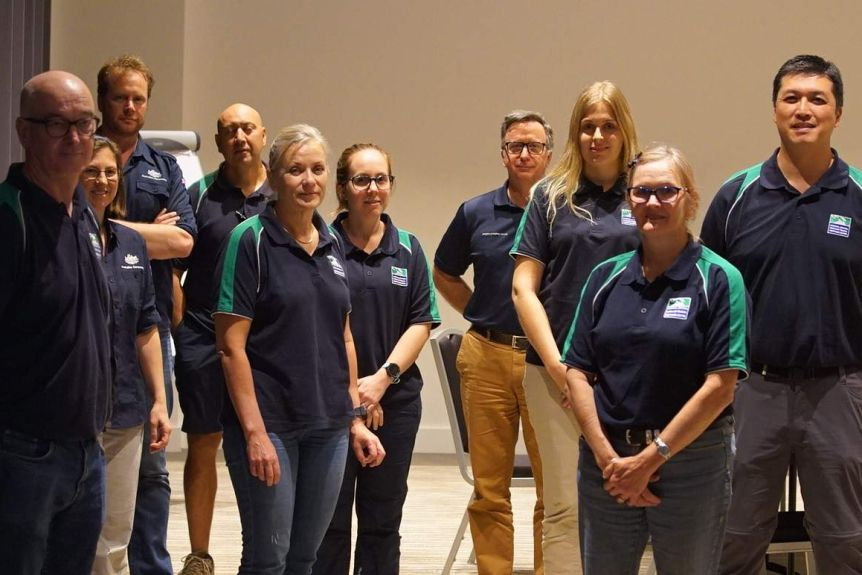 A group of Australian DFAT workers in blue polo shirts