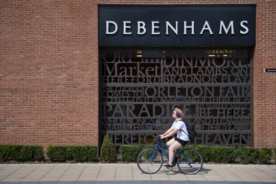 A woman cycles past a Debenhams store on August 11, 2020 in Hereford, England. Debenhams has announced that 2,500 jobs are to be cut. Many UK businesses are announcing job losses due to the effects of the coronavirus pandemic and lockdown.