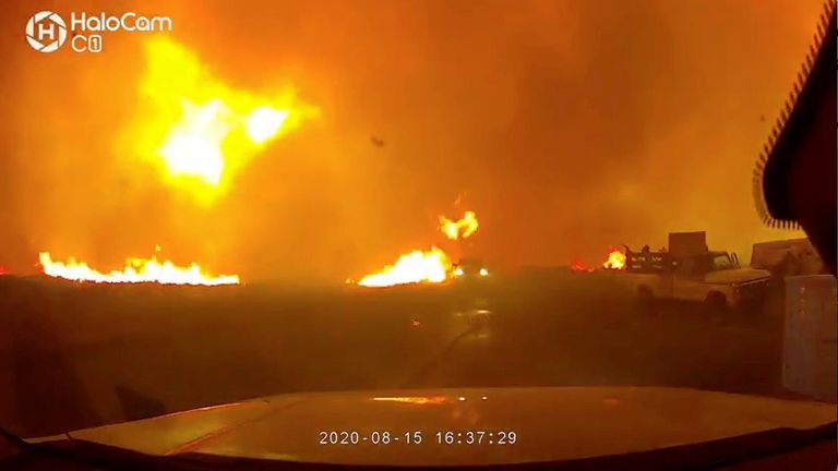 Firefighters drive to safety from massive Loyalton Fire next to highway in Chilcoot, California, U.S. August 15, 2020, in this still image obtained from a social media video. Courtesy of Truckee Meadows Fire And Rescue/Social Media via REUTERS. ATTENTION EDITORS - THIS IMAGE HAS BEEN SUPPLIED BY A THIRD PARTY. MANDATORY CREDIT TRUCKEE MEADOWS FIRE AND RESCUE. NO RESALES. NO ARCHIVES.