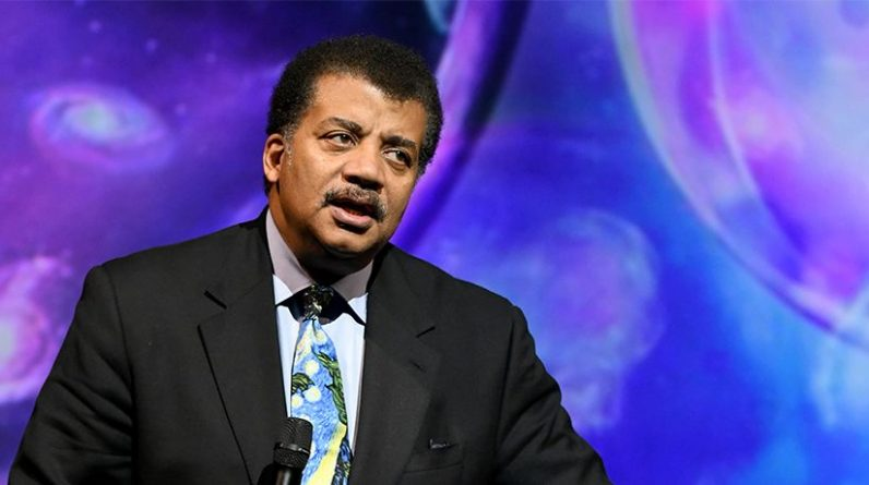 Neil Degrasse Tyson stands in front of a blue and purple screen.