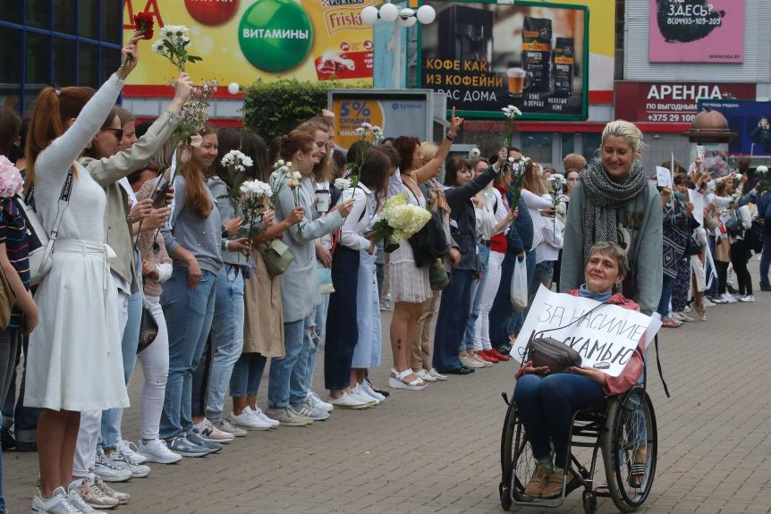 A woman pushes a woman in a wheelchair past a long chain of women holding white flowers aloft, waving hands and smiling.
