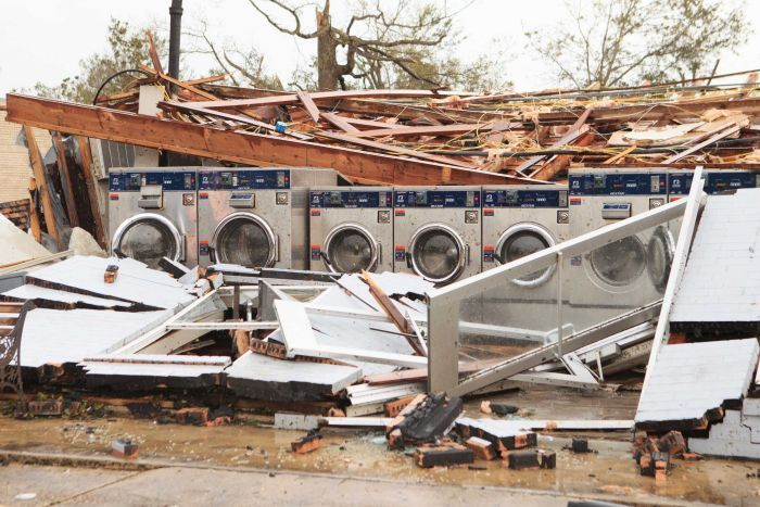 A row of washing machine stand in the middle of a collapsed building.