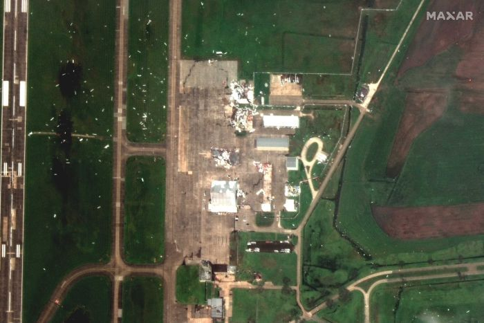 Scattered buildings are seen destroyed and surrounded by debris from a satellite image.