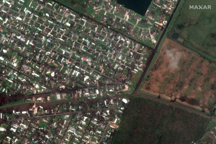Homes are seen surrounded by debris from a satellite image.