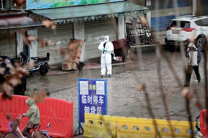 A man in a hazmat suit standing outside a Chinese marketplace