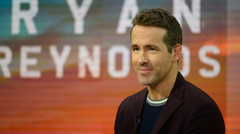 Ryan Reynolds smiling in front of an orange and blue background