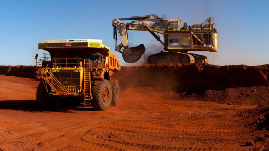 An earth mover shifts dirt into a truck in the Pilbara