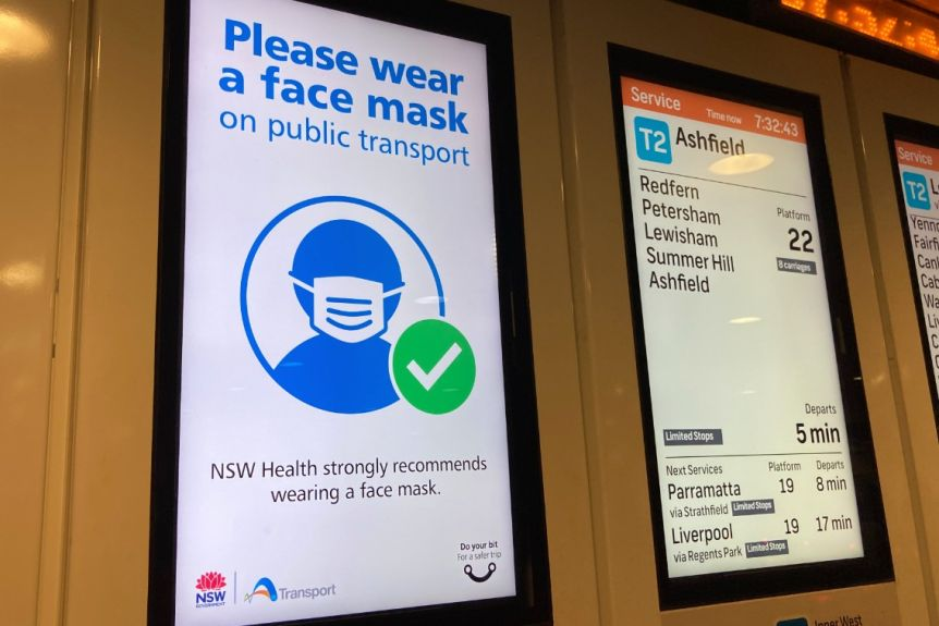 """A sign at a train station says: """"Please wear a face mask on public transport""""."""