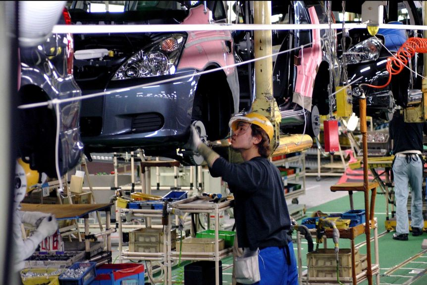 A man works on the Toyota motor plant assembly line.