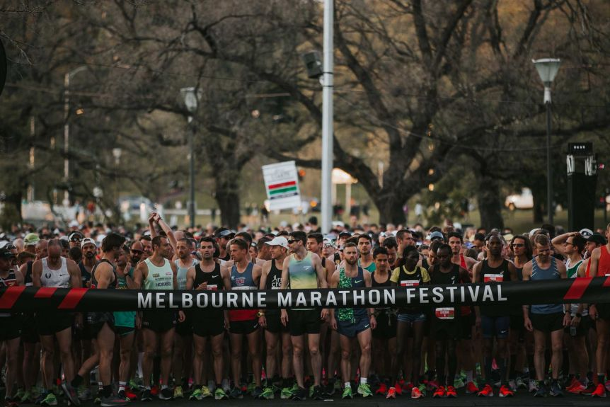 A group of runners stands in front of Ribbon for a mass race on a leafy city street.