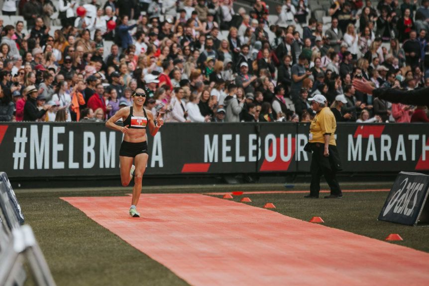 The smiling female runner gives a thumbs up on the track running behind with a large crowd.