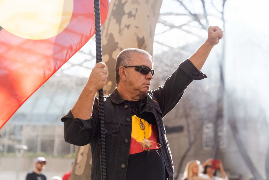 """An opponent holds a tribal flag and his fist in the air """"Black power"""" Signal."""