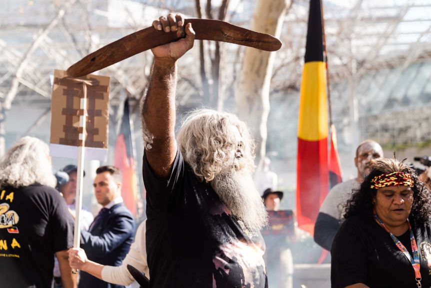 A man holds a boomerang in the air, behind him is a tribal flag, and a woman wearing a red, yellow and black helmet with feathers.