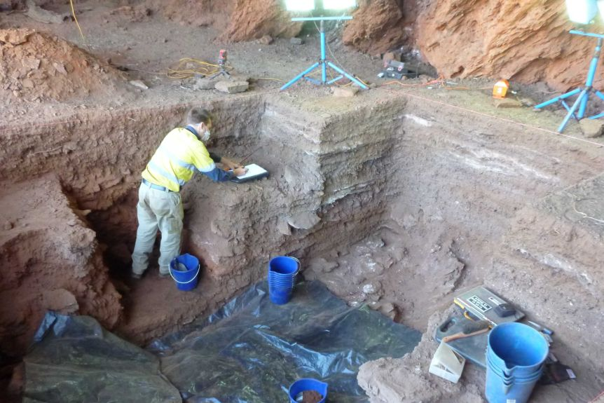 A man inside a pit makes notes while excavating artifacts.