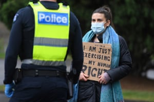 A woman with an identity card speaks to police during a protest in Melbourne.
