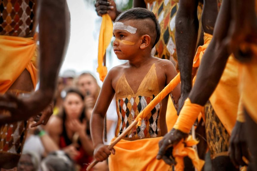 A young tribal boy dances and his body is decorated with traditional pigment marks.