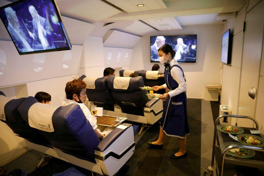 Staff dressed as flight attendants serve food to customers on a fake flight.