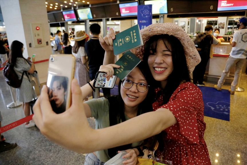 Two women take a selfie with their passports in front of a check-in counter at an airport.