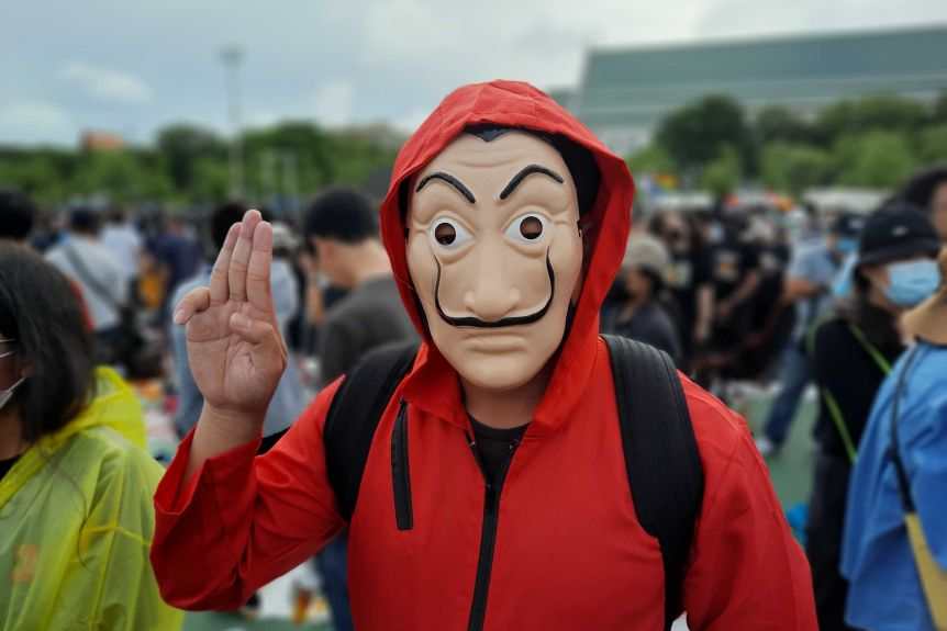 Someone in a red hoodie and anonymous mask salutes with three fingers.