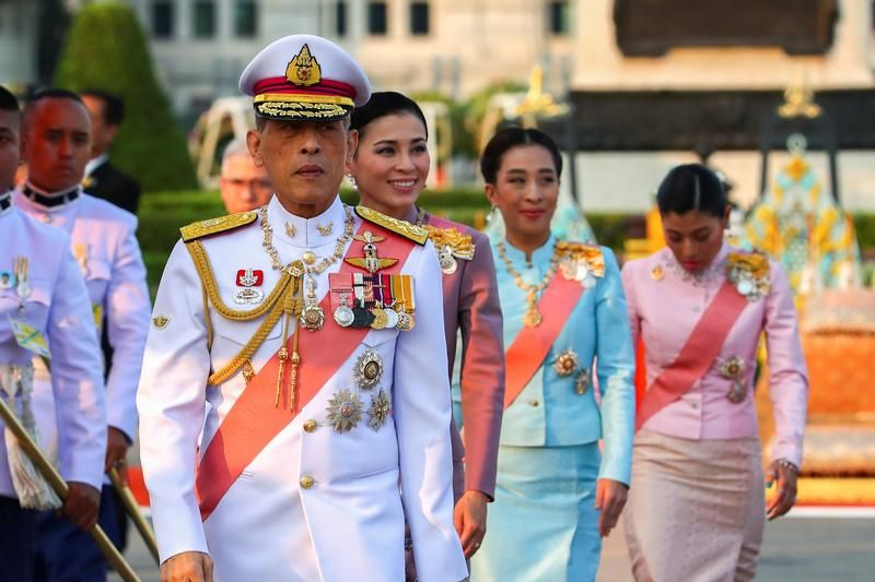 King Vajiralongkorn of Thailand walks in traditional white uniform during the parade.