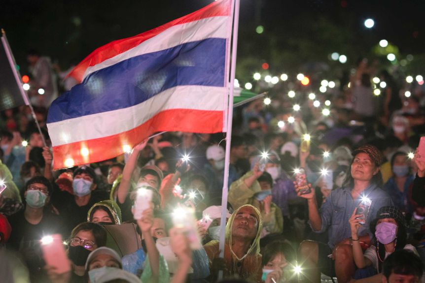 People sitting in raincoats waving Thai flag at night with lights from smartphones