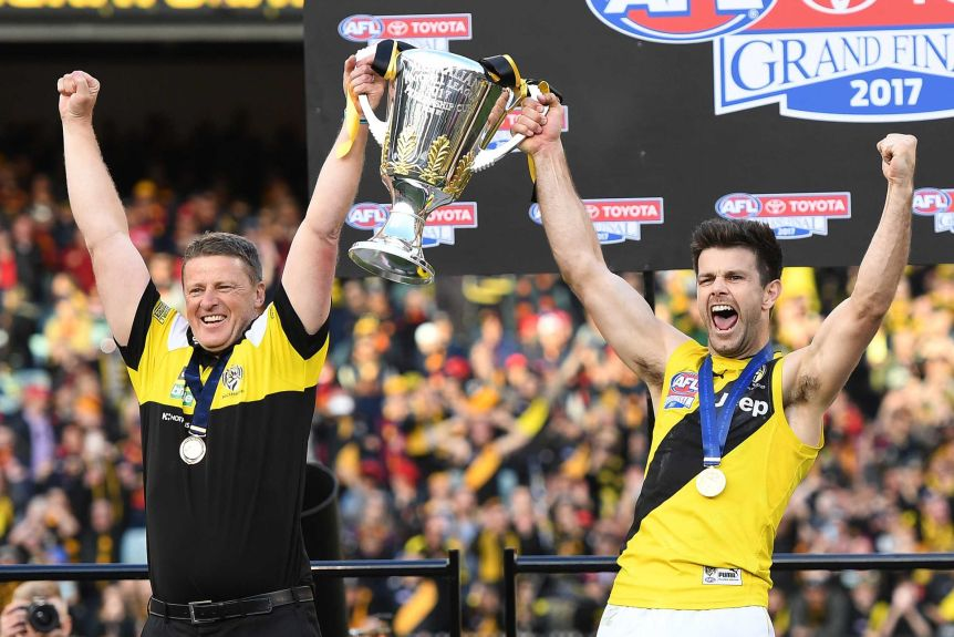 Damien Hardwick and Trent Kotzin cheer as they lift the Premiership trophy.