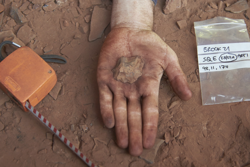 One hand holds out a rock, and in the background is the dust on the base of the Jukan rock cave.