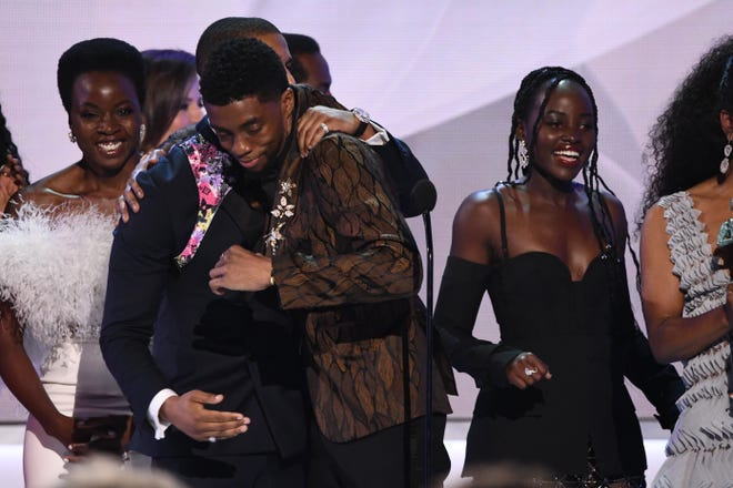 "Michael B. Jordan (L) congratulates Chadwick Boseman (C) as the cast of ""Black Panther"" accepts an award at the 25th Annual Screen Actors Guild Awards on Jan 27, 2019."