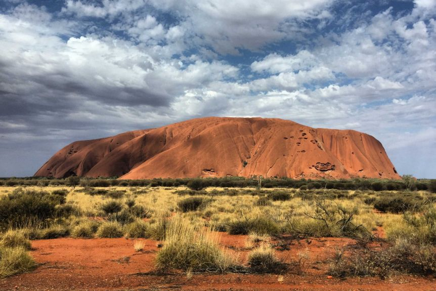 Uluru against the cloudy blue skies.