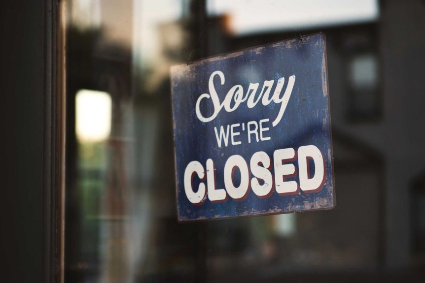 """A sign reading """"Sorry we closed"""" Hanging on a window."""