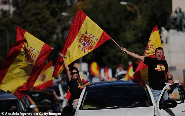 Supporters of the far-right Vox party hold Spanish flags and take part in a motorcade against the lockout