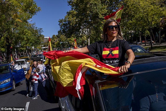 A demonstrator waves the Spanish flag while wearing a T-shirt that reads Sanchez and Iglesias. Get out now! '