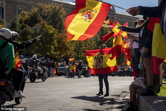 A protester holds a pre-constitutional Spanish flag as a motorcyclist pays homage to a fascist on Costellana Street.